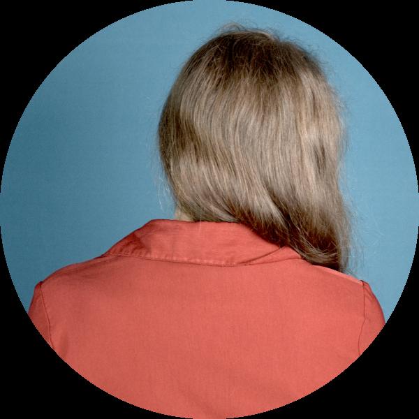 Foto einer Frau von der Rückseite. Sie hat offenes, zur Seite getragenes Haar und trägt eine leuchtend rote Bluse. Der Hintergrund ist petrol-farben.